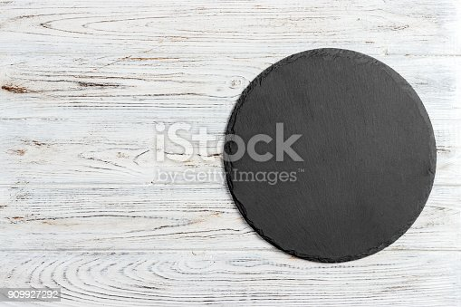 istock Black slate round stone on wooden background, top view, copy space 909927292