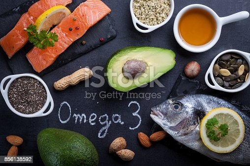 istock Black slate table with product rich in omega 3 and vitamin D. Written word omega 3 by white chalk. 856138592