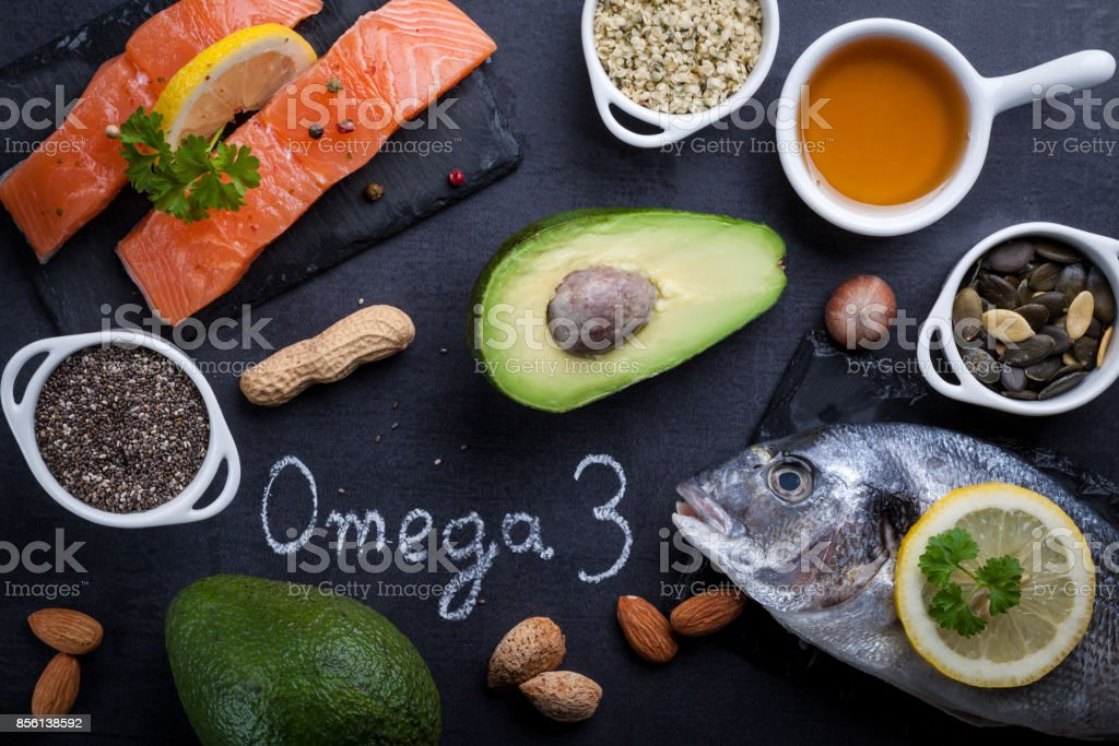 Black slate table with product rich in omega 3 and vitamin D. Written word omega 3 by white chalk. stock photo