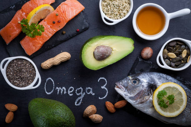 mesa pizarra negro con productos ricos en omega 3 y vitamina d. escrito omega 3 de la palabra tiza blanca. - omega 3 fotografías e imágenes de stock