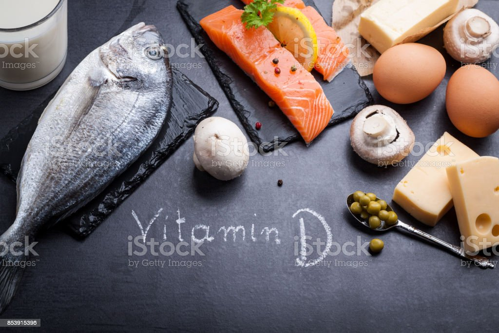Black slate table with product rich in vitamin D and omega 3. Written word vitamin D by white chalk. royalty-free stock photo