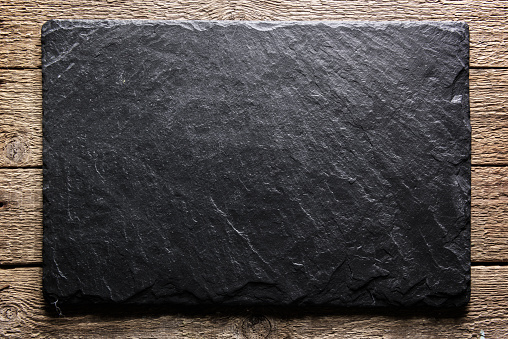 Black slate board on grunge wooden table closeup. Natural texture. Can be used like food background