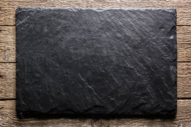 Black slate texture closeup Black slate board on grunge wooden table closeup. Natural texture. Can be used like food background marble rock stock pictures, royalty-free photos & images