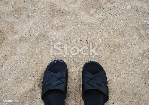 istock Black slippers on a background of sand 639664970
