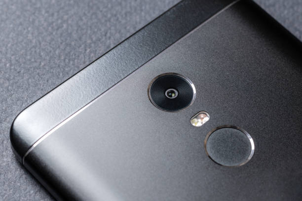 black smartphone on a black textured surface is the back side - sale lenses stock photos and pictures