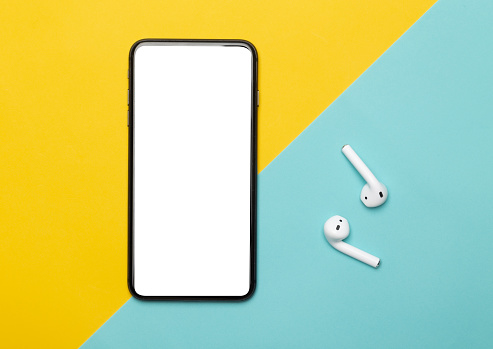 Black smartphone with blank screen and wireless earphones isolated on yellow and blue background. Clipping path.