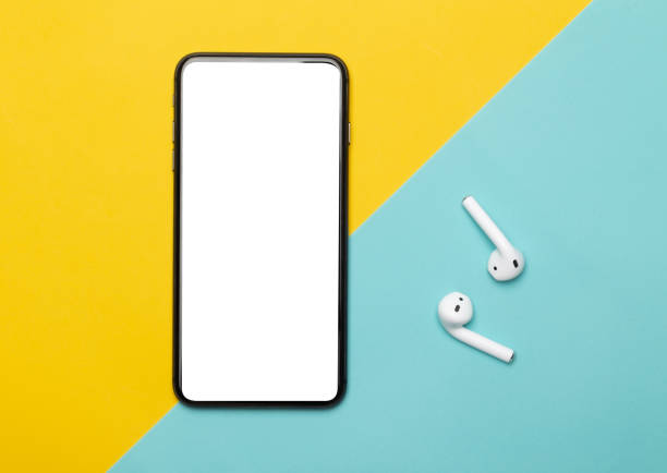 Black smartphone with blank screen and wireless earphones isolated on yellow and blue background. Clipping path Black smartphone with blank screen and wireless earphones isolated on yellow and blue background. Clipping path. wireless headphones stock pictures, royalty-free photos & images