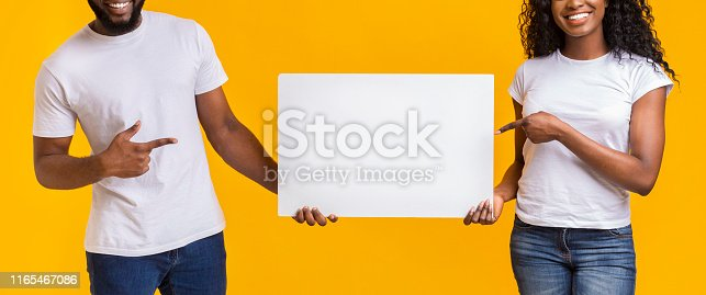 1168002879 istock photo Black smiling couple is pointing at blank 1165467086