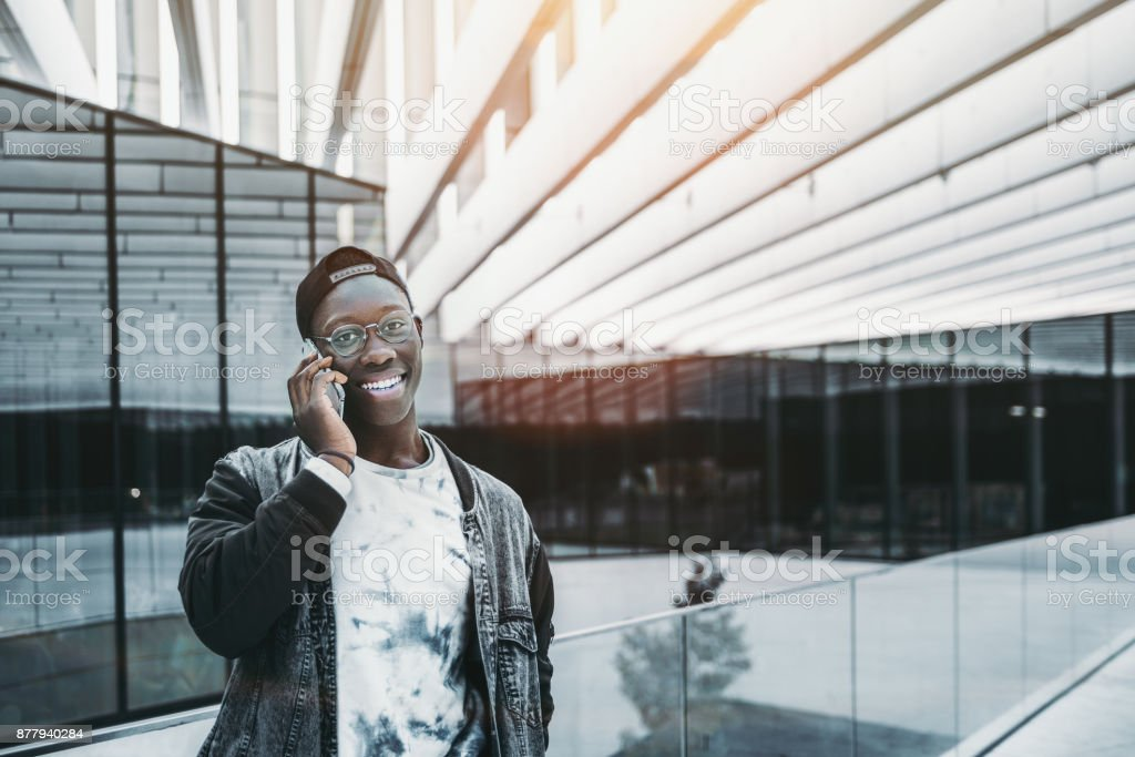 Black smiling guy is talking on the phone stock photo