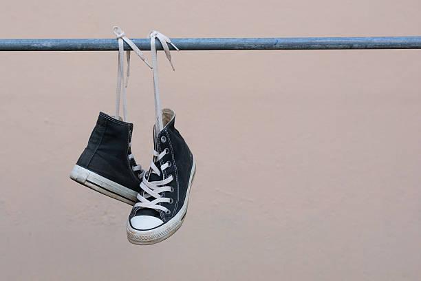 black sneakers hanging on metal bar - kabelschuhe stock-fotos und bilder
