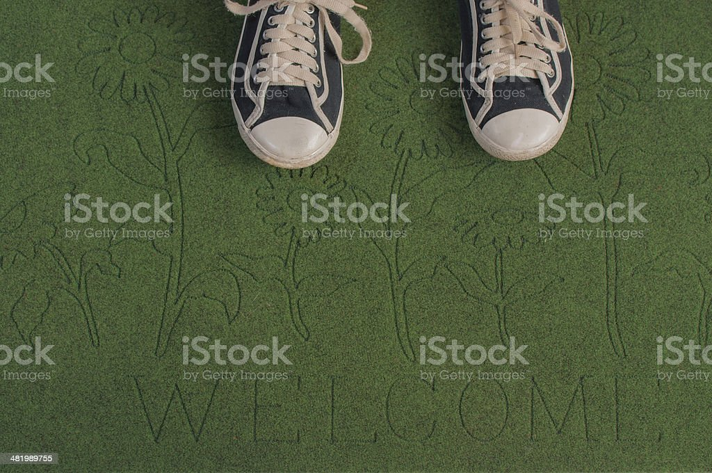 Black sneakers on a green welcome mat stock photo