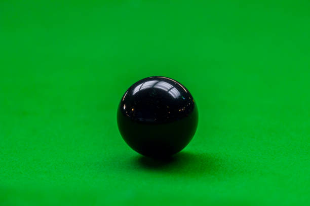 Black snooker ball on green table background stock photo