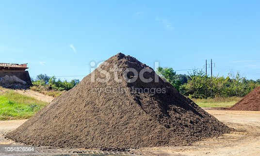 Mound of black Soil used for landscaping and driveways on display and for sale.