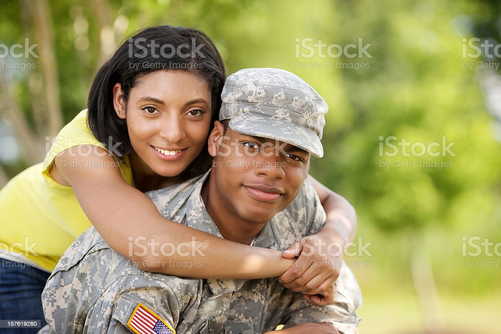 Black soldier in camouflage with his girlfriend in yellow royalty-free stock photo