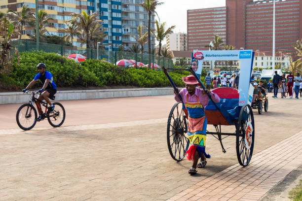 A black south african man carrying a rickshaw without passengers at the beach front of Durban, South Africa. stock photo