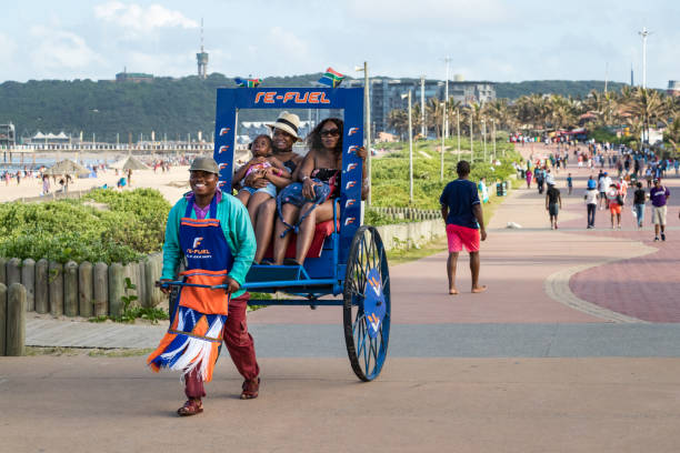 A black south african man trasporting a family using a rickshaw at the beach front of Durban, South Africa. stock photo