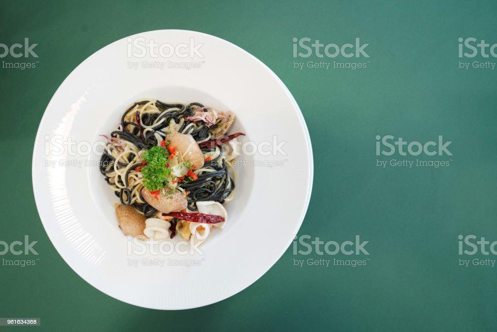 Black spaghetti seafood garlic fry on the table stock photo