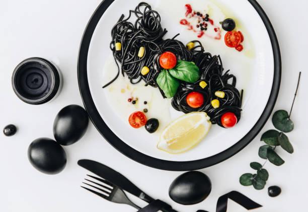 schwarze spaghetti mit basilika und tomaten auf den tisch. schwarz-ostereier. - pasta deli stock-fotos und bilder