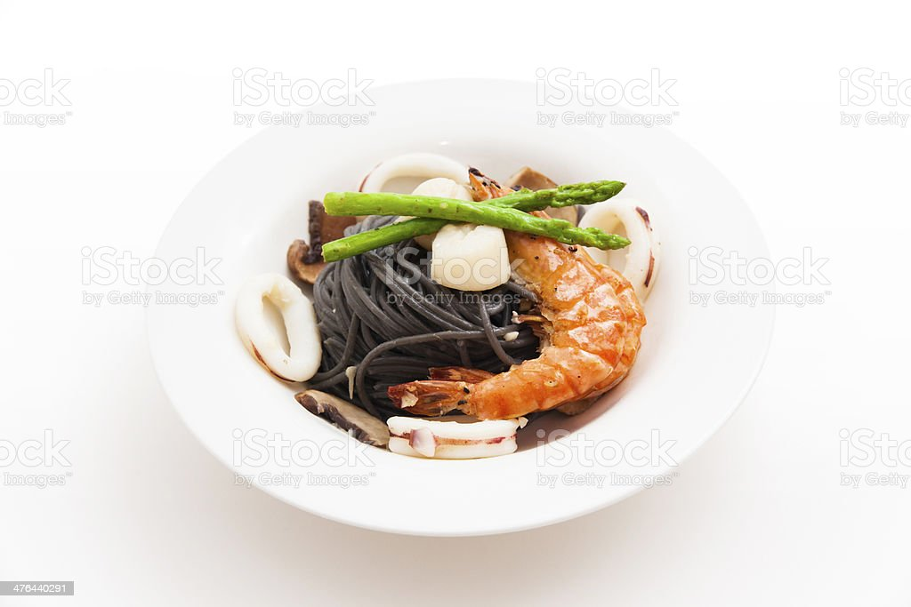 Black spaghetti with seafood on white background (squid ink pasta) royalty-free stock photo