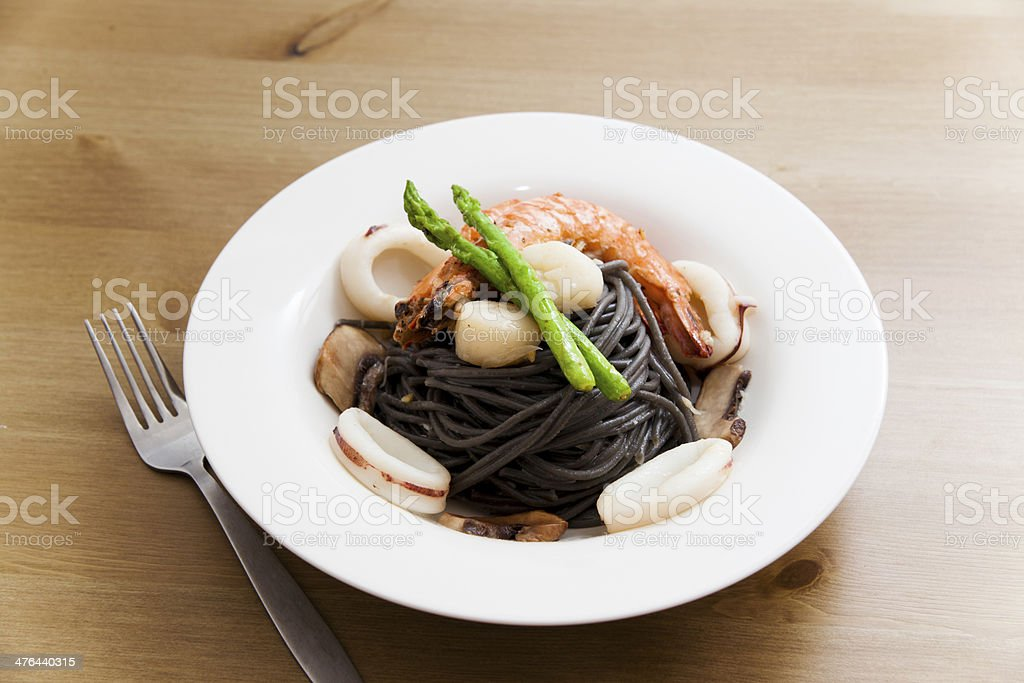 Black spaghetti with seafood on wooden table (squid ink pasta) royalty-free stock photo