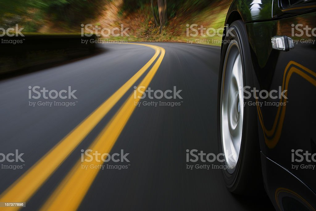 A black sports car driving around a curve stock photo