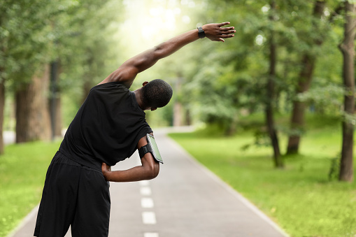Black sportsman exercising before jogging at park, back view, copy space