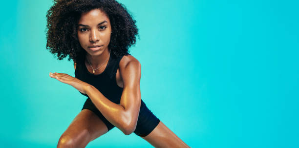 Black sporty female exercising in fitness studio Healthy african woman working out. Black sporty female exercising in fitness studio, looking at camera. jacoblund stock pictures, royalty-free photos & images