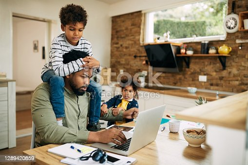 Distraught African American father using laptop and working at home while being distracted by his small children.