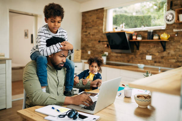 Black stay at home father working on laptop while his kids are demanding his attention. stock photo