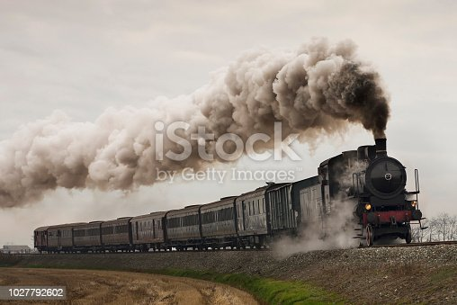 Vintage black steam train running on rails in a foggy day
