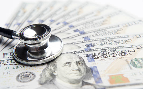 Black stethoscope laying on top of money stock photo