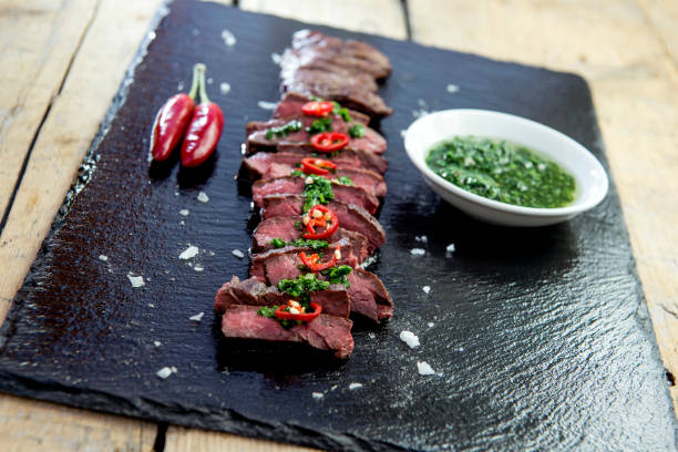 schwarzen steinplatte mit rock steak pfeffer und chimichurri-sauce - flank steak marinaden stock-fotos und bilder