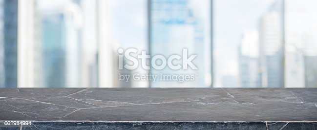 662984808 istock photo Black Stone table top and blur glass window wall building banner background 662984994