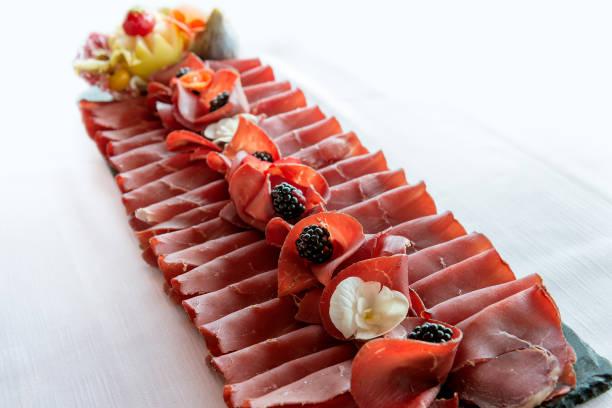 black stone tray with sliced bresaola - bresaola foto e immagini stock
