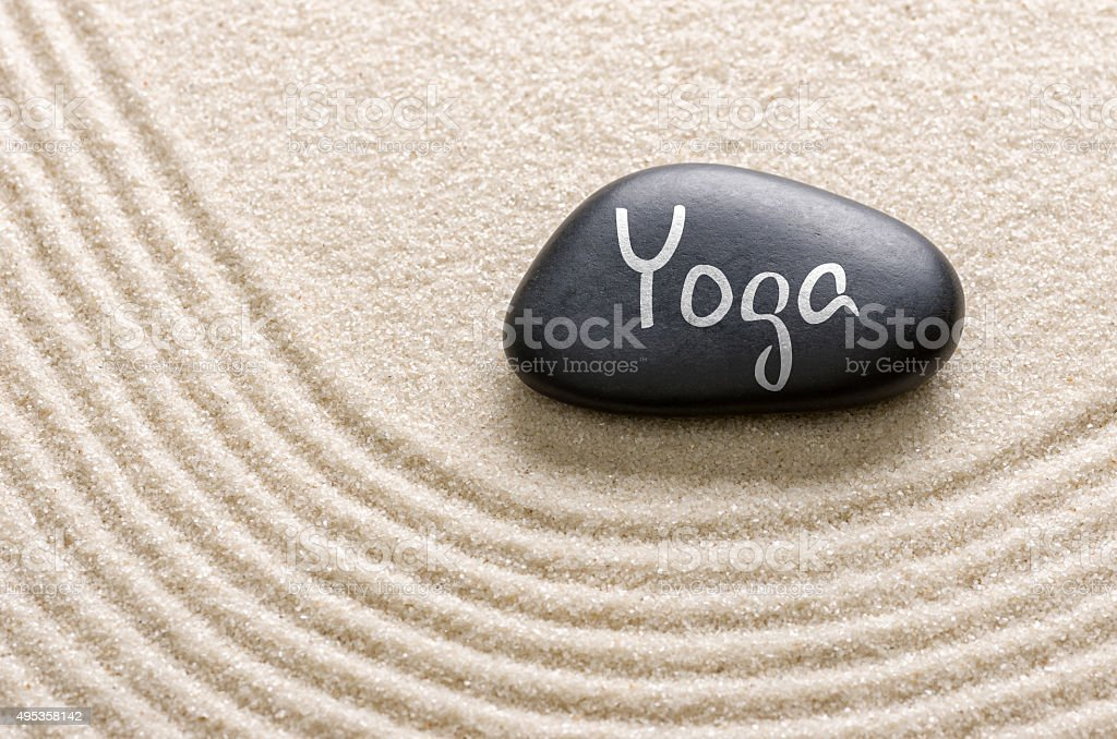 Black stone with the inscription Yoga stock photo