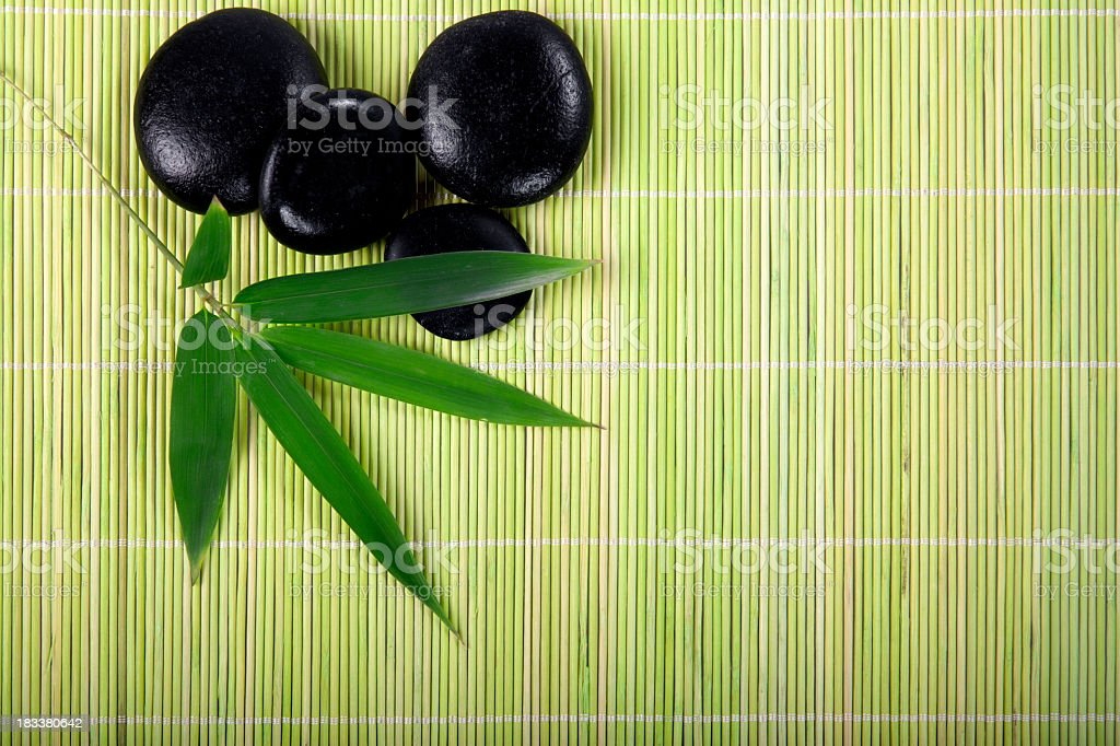 Black stones with bamboo leaf in a zen spa stock photo