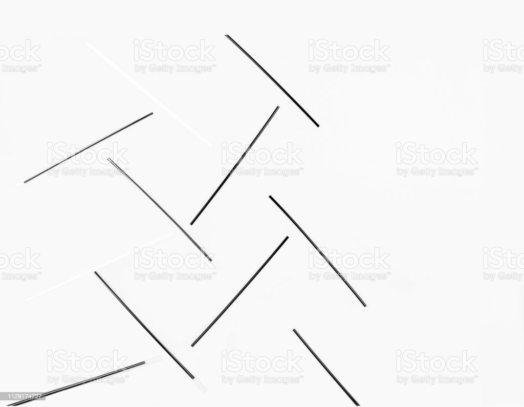 Black straws lay geometrical on a white background. Straws is a small...