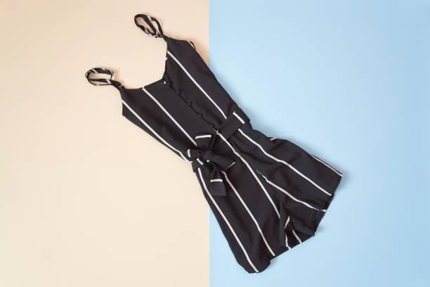 schwarz gestreifter strampler, zart rosa und blauen hintergrund. modische konzept - jumpsuit blau stock-fotos und bilder