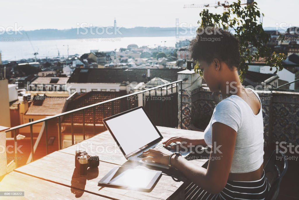 Black student girl with laptop on balcony stock photo