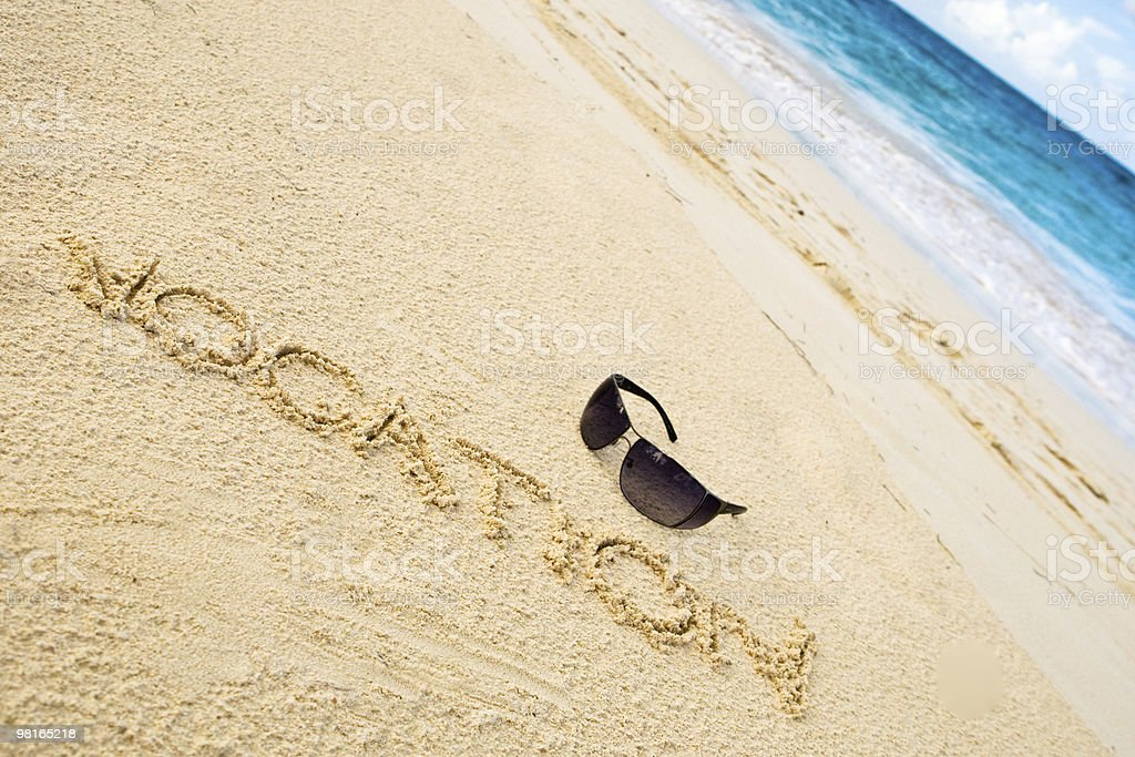 Black sun glasses on white sand beach and word vocation royalty-free stock photo