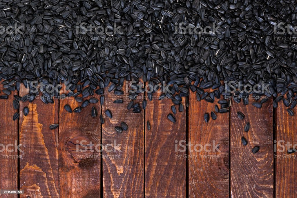 Black sunflower seeds on wooden background, top view, copy space stock photo