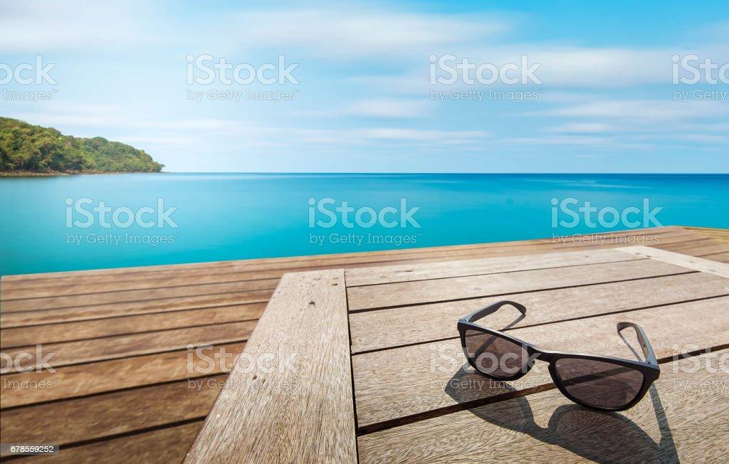 black sunglass on wood terrace at seaside stock photo