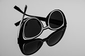 Black sunglasses with a white insert on a dark surface with reflection.