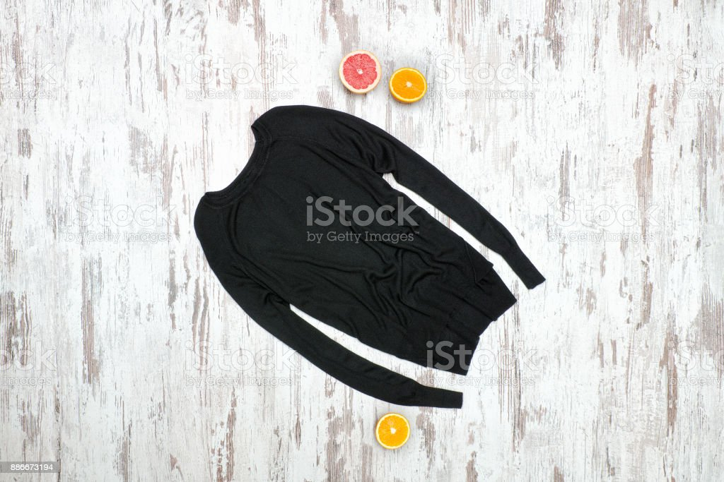 Black sweater on a wooden background, halves of citrus. Fashionable concept stock photo