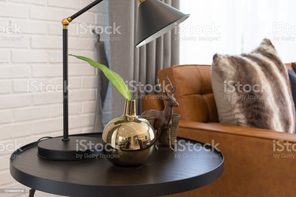 Black table lamp with vase and brown leather sofa in industrial style...