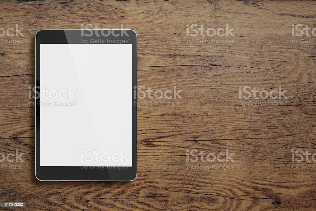 Black tablet pc on old wood table background stock photo