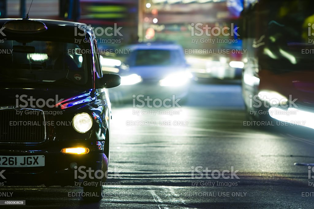 Black Taxi Cab in Night Traffic, Piccadilly Circus, London, UK stock photo