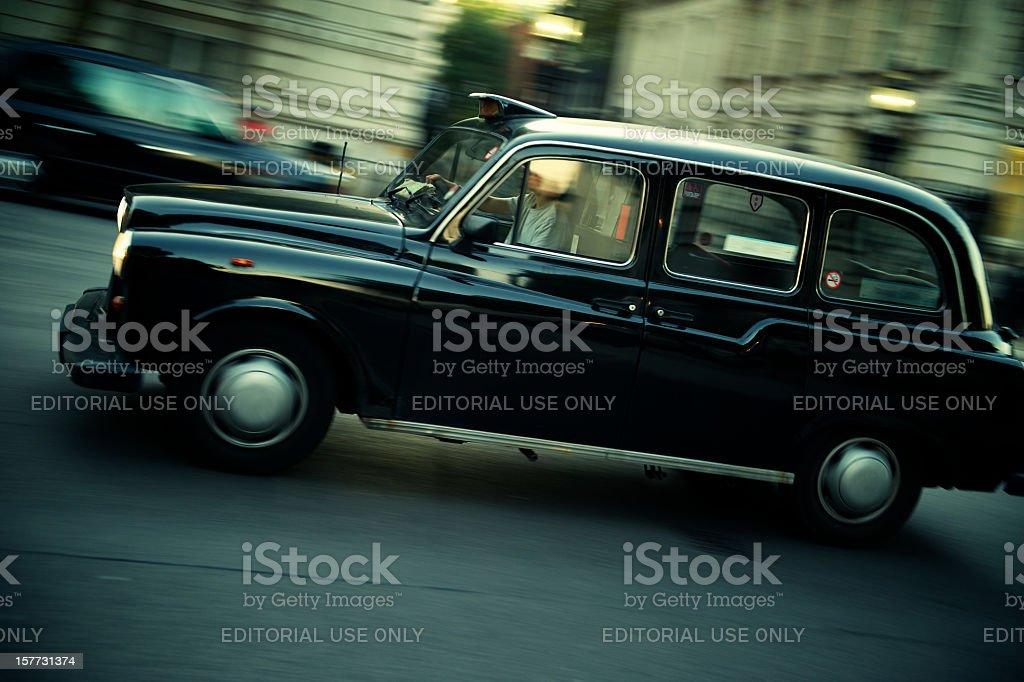 Black Taxi Drives on London Street stock photo