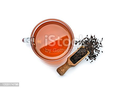 Black tea cup shot from above on white background. A wooden serving scoop with dried black tea leaves is beside the tea cup. High resolution 42Mp studio digital capture taken with Sony A7rii and Sony FE 90mm f2.8 macro G OSS lens