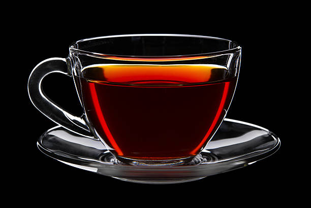 Black tea in a glass cup and saucer on a black background stock photo